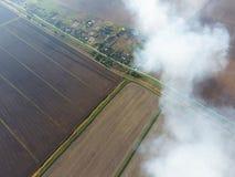 Der Rauch über dem Dorf Clubs des Rauches über dem Dorf bringt und Felder unter Aerophotographing-Bereiche Stockfotografie