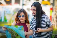 Der recht junge weibliche Tourist, der eine Karte studiert mit abstraktem GR Stockbild