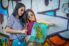Der recht junge weibliche Tourist, der eine Karte studiert mit abstraktem GR Stockbilder