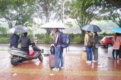 Der Regen, der auf Busausgangsleute wartet Lizenzfreie Stockbilder