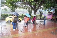 Der Regen, der auf Busausgangsleute wartet Stockfotografie