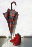 Der Regenschirmstock und die roten Gummistiefel Stockbild