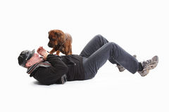 Der reife Mann, der an liegt, unterstützen mit Hund Lizenzfreies Stockfoto