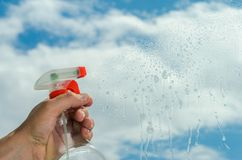 Der Reiniger säubert die Fenster mit einem Reinigungsmittel lizenzfreies stockfoto