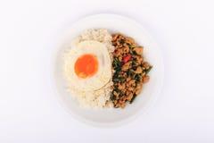 Der Reis, der mit angebratenem Huhn, Basilikum und Spiegelei überstiegen wurde, briet Aufruhrbasilikum mit gehacktem Huhn auf wei Lizenzfreies Stockbild