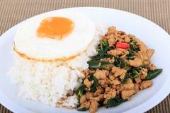 Der Reis, der mit angebratenem Huhn, Basilikum und Spiegelei überstiegen wurde, briet Aufruhrbasilikum mit gehacktem Huhn auf wei Lizenzfreie Stockfotos