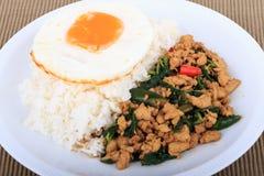 Der Reis, der mit angebratenem Huhn, Basilikum und Spiegelei überstiegen wurde, briet Aufruhrbasilikum mit gehacktem Huhn auf bra Lizenzfreie Stockbilder