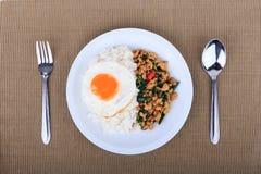 Der Reis, der mit angebratenem Huhn, Basilikum und Spiegelei überstiegen wurde, briet Aufruhrbasilikum mit gehacktem Huhn auf bra Lizenzfreies Stockfoto