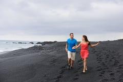 Der Reisefeiertage der Paare gehender schwarzer Sandstrand Stockfotografie