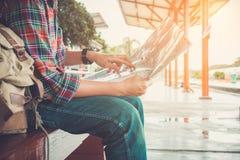 der Reisende des jungen Mannes, der mit Karte sitzt, wählen, wohin man wai reist Stockfoto