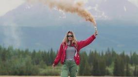 Der Reisende gibt ein Zeichen und erregt Aufmerksamkeit mit farbigem Rauche touristisches Mädchen, das eine Rauchbombe hält Langs stock video footage