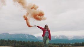 Der Reisende gibt ein Zeichen und erregt Aufmerksamkeit mit farbigem Rauche touristisches Mädchen, das eine Rauchbombe hält Langs stock video