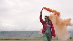 Der Reisende gibt ein Zeichen und erregt Aufmerksamkeit mit farbigem Rauche touristisches Mädchen, das eine Rauchbombe hält Langs stock footage