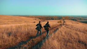 Der Reisende mit zwei Männern, der mit Rucksäcken wandert, gehen entlang den Weg, der in die Berge klettert Zeitlupevideo stock footage