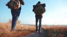 Der Reisende mit zwei Männern, der mit Rucksäcken wandert, gehen entlang den Weg, der in die Berge klettert Zeitlupevideo stock video footage