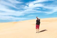 Der Reisende steht unter den weißen Dünen lizenzfreies stockbild