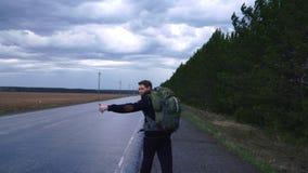 Der Reisende versucht, das Auto im wolkigen Wetter zu stoppen stock footage
