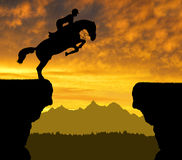Der Reiter auf dem Pferd, das über einen Abstand springt Stockfoto