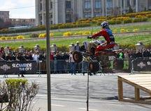 Der Reiter springend von einer Rampe mit dem Viererkabel Lizenzfreie Stockfotografie