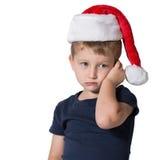 Der reizend kleine Junge in der roten Kappe von Santa Claus Stockfoto