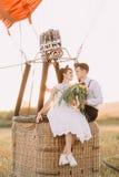 Der reizende Blickkontakt zwischen den Weinlese gekleideten Jungvermählten, die auf dem airballon Korb gelegt auf dem sonnigen Ge Lizenzfreies Stockfoto