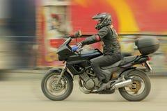 Der Rennläufermotorradfahrer, der einen Sturzhelm trägt, reitet um Stadt Lizenzfreies Stockbild