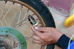 Der Reparaturmann füllen die Luft in das motocycle Rad auf lizenzfreies stockbild