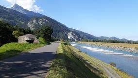 Der Rhein- und Fahrradweg mit Berg und blauem Himmel auf dem Hintergrund Lizenzfreies Stockbild
