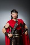 Der römische Krieger mit Klinge gegen Hintergrund Lizenzfreie Stockfotografie