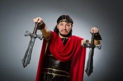 Der römische Krieger mit Klinge gegen Hintergrund Stockfotografie