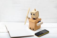 Der Roboter hält den Griff des Kraftpapiers und schrieb in Tagebücher Lizenzfreies Stockbild