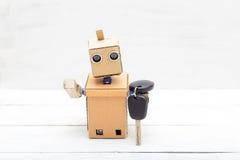 Der Roboter hält die Autoschlüssel in seiner Hand lizenzfreies stockbild