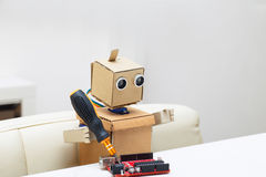 Der Roboter hält einen Schraubenzieher am Tisch Stockfotos