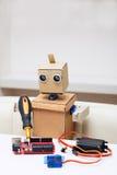 Der Roboter hält einen Schraubenzieher und lötet den roten Chip auf dem Tisch Lizenzfreies Stockfoto
