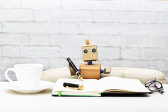 Der Roboter sitzt am Tisch und hält einen Stift für das Schreiben Lizenzfreie Stockbilder