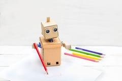 Der Roboter zeichnet ein Bleistiftherz auf einem Blatt Papier Stockfotografie