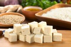 Der rohe Tofu, der eingeschnitten wird, würfelt Stockfoto