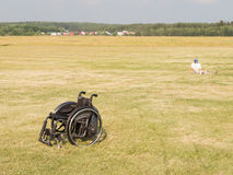 Der Rollstuhl und die Person, die auf dem Gras, Moskau Regio sitzen Stockfotos