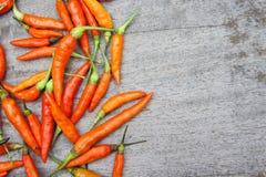 Der rote Paprika, der auf hölzerner Tabelle roh ist, bereiten Lebensmittel geben einen würzigen Geschmack zu Lizenzfreies Stockbild