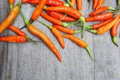 Der rote Paprika, der auf hölzerner Tabelle roh ist, bereiten Lebensmittel geben einen würzigen Geschmack zu Stockfotos