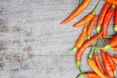 Der rote Paprika, der auf hölzerner Tabelle roh ist, bereiten Lebensmittel geben einen würzigen Geschmack zu Lizenzfreie Stockbilder