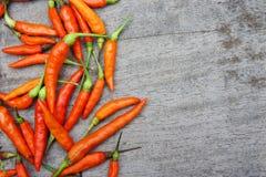 Der rote Paprika, der auf hölzerner Tabelle roh ist, bereiten Lebensmittel geben einen würzigen Geschmack zu Lizenzfreies Stockfoto