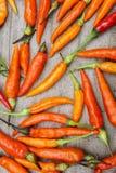 Der rote Paprika, der auf hölzerner Tabelle roh ist, bereiten Lebensmittel geben einen würzigen Geschmack zu Stockbild