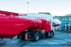 Der rote Tanker, der die Flugzeuge geparkt zu einer Landungsbrücke am Flughafenschutzblech wieder tankt lizenzfreies stockfoto
