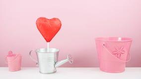 Der rote vereitelte Schokoladenherzstock mit kleiner silberner Gießkanne und kleinem rosa Eimer Stockbilder
