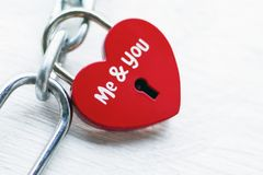 Der rote Verschluss in Form von Herzen auf einer Eisenkette mit einer Aufschrift, mir und Ihnen Das Konzept der Liebe und der Hei stockbild