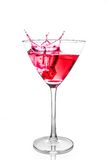 Der rote Würfel, der in das rote Cocktailglas mit fällt, spritzt Lizenzfreies Stockfoto