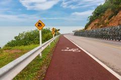 Der rote Weg für Fahrrad auf der Straße zwischen Küste und mountai Lizenzfreie Stockbilder