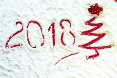 Der rote Weihnachtsbaum, der auf Schnee gemalt werden und das neue Jahr simsen 2018 Stockfotografie