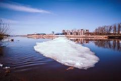 Der ruhig fließende Fluss fließt in Vorfrühling, als es noch Eis und Schnee gibt Frühlingsstadtbild lizenzfreie stockfotografie